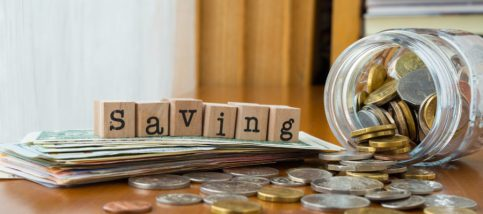 Saving word on rubber stamps place on banknotes with coins spilling out of money jars